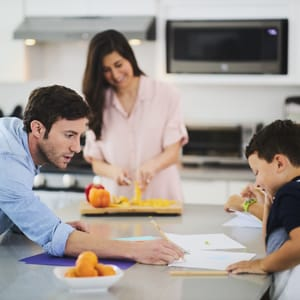 dad helping son with homework while mom makes dinner