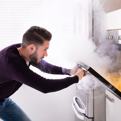 man opens oven and cooking smoke billows out