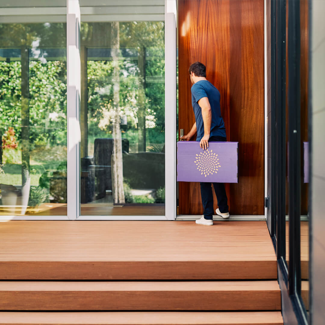 man walking through front door with second nature box
