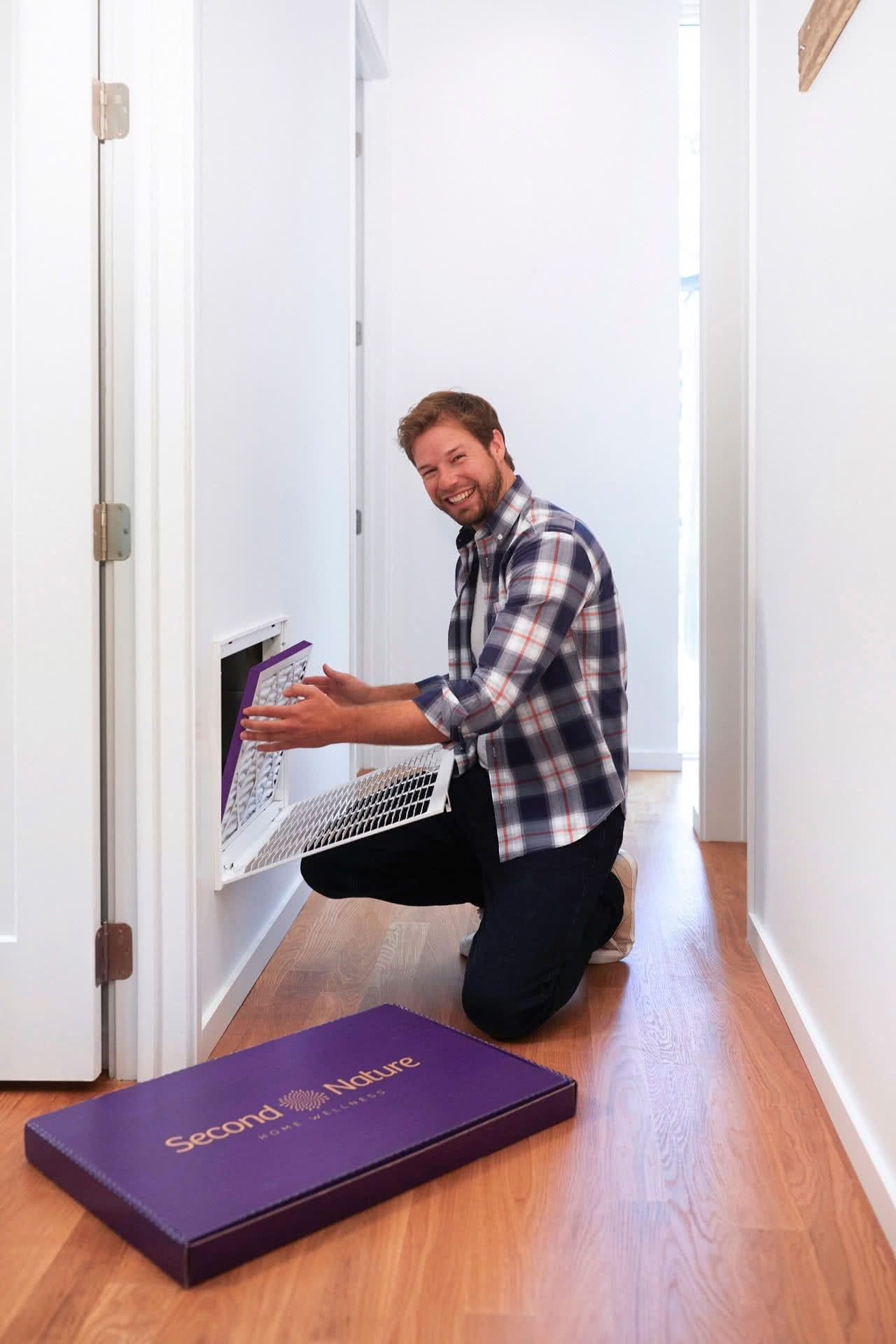 man replacing air filter in home
