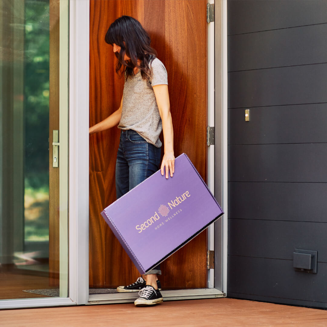 woman walks in front door with second nature box