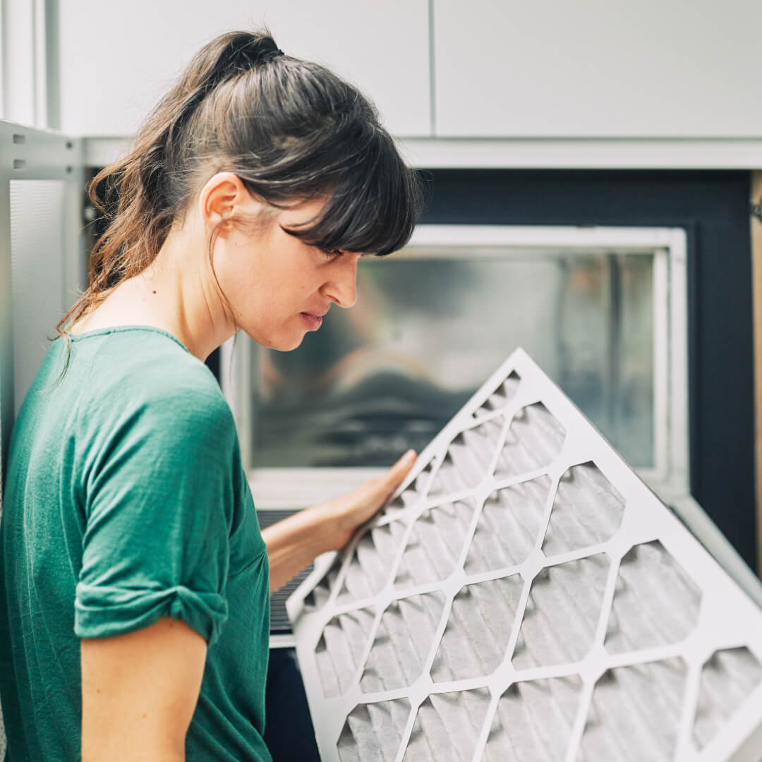 woman looks at filter in front of vent