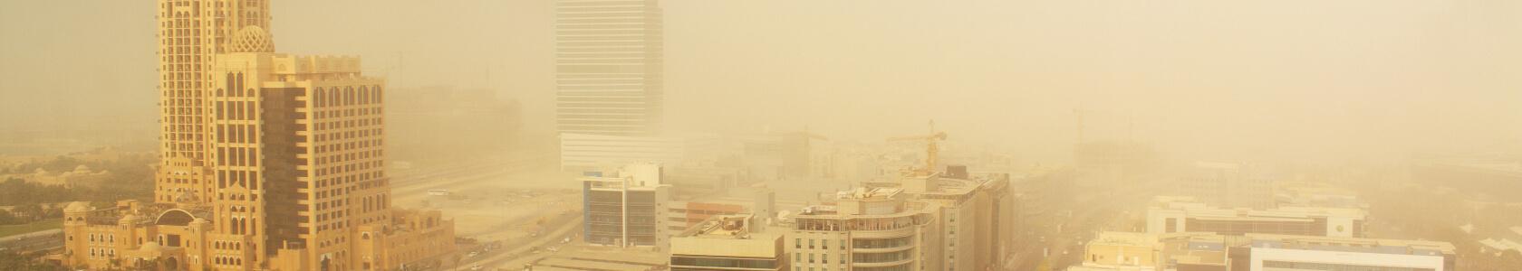 a dust cloud descends over a city
