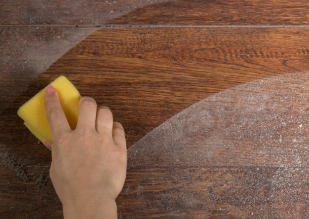 hand dusting a wood surface