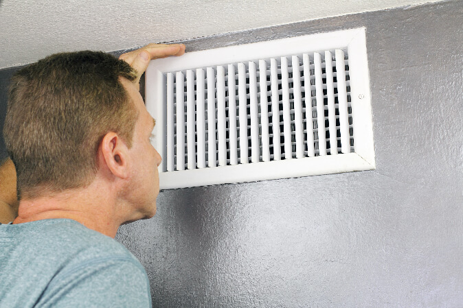 man looking into air vent